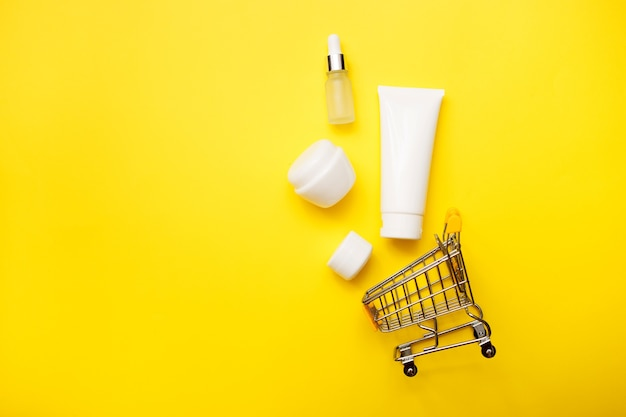 Cosmetics bottles with supermarket trolley on bright yellow background, top view, copy space. mock up. white jars, bath accessories. face, body care and online concept.