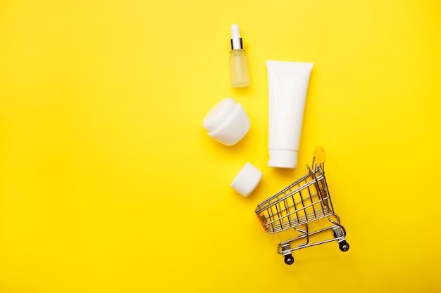 明るい黄色の背景、平面図、コピースペースにスーパーマーケットのトロリーと化粧品ボトル。モックアップ。白い瓶、バスアクセサリー。顔、ボディケア、オンラインのコンセプト。