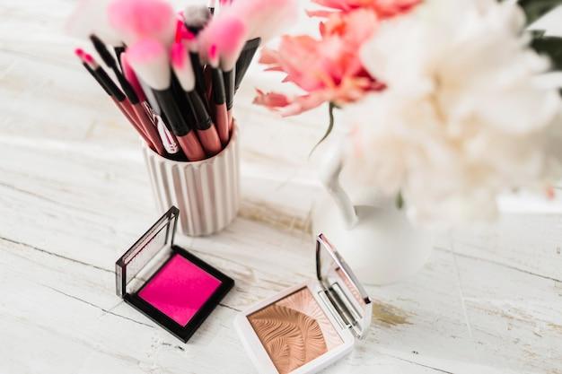 Cosmetici e pennelli vicino ai fiori