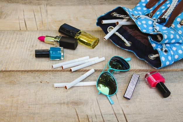 Cosmetics and cigarettes fell out of the backpack of a teenager on a wood