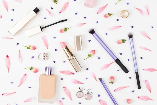 白い背景の上の口紅のブラシや他のアクセサリーと化粧品のコラージュ