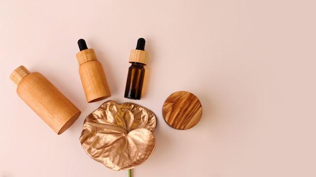 木の化粧品容器は金色のフラミンゴの花の周りにあります。コピースペースのあるパステル背景。ゼロウェイスト、有機製品、大きなバナーの概念。