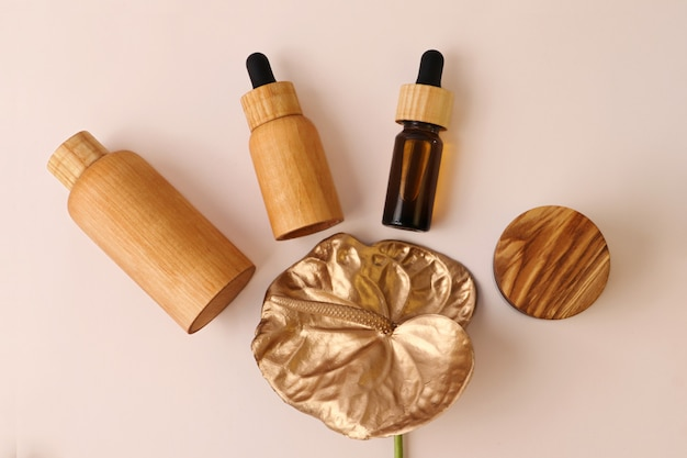 Cosmetics containers from wood lie around golden flamingo flowerpastel background