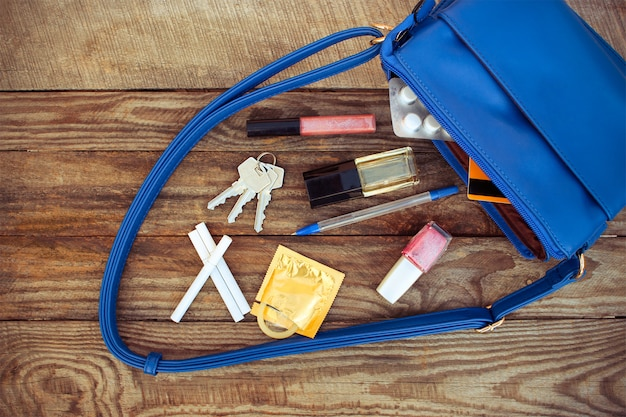 Cosmetics, female accessories, birth control pill, cigarette and condom falls out of pocket with handbags