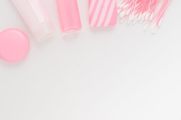 美容とスキンケア、メイクアップのための化粧品。泡のクレンジング、保湿、にきびやしわからの栄養、強壮剤、リップクリーム、綿棒、コピースペース付きのピンクの背景に天然石鹸