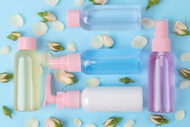 부드러운 파란색 배경에 신선한 장미와 함께 분홍색 병에 얼굴과 몸을 위한 화장품. 크림과 로션. 온천. 평면도