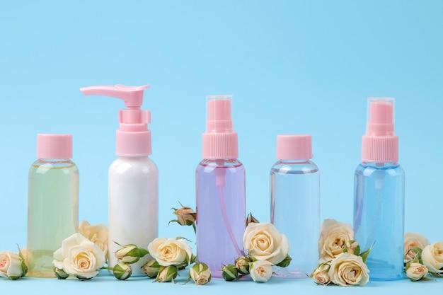 부드러운 파란색 배경에 신선한 장미와 함께 분홍색 병에 얼굴과 몸을 위한 화장품. 크림과 로션. 온천.