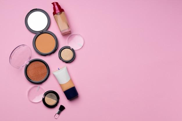 분홍색 배경에 얼굴 안색을위한 화장품을 닫습니다.