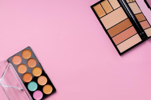 ピンクの背景に顔の顔色のための化粧品