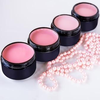 핸드 케어용 화장품. 흰색 바탕에 밤용 젤의 색상을 강조하는 검정 도즈 및 핑크 진주 구슬의 네일 플레이트용 컬러 코팅