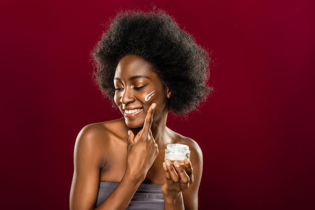 肌用化粧品。彼女の頭を回しながら笑っているポジティブなうれしそうな素敵な女性