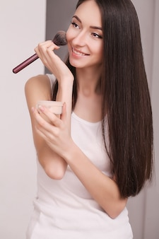 Cosmetics, health and beauty  - beautiful woman with closed eyes and makeup brush