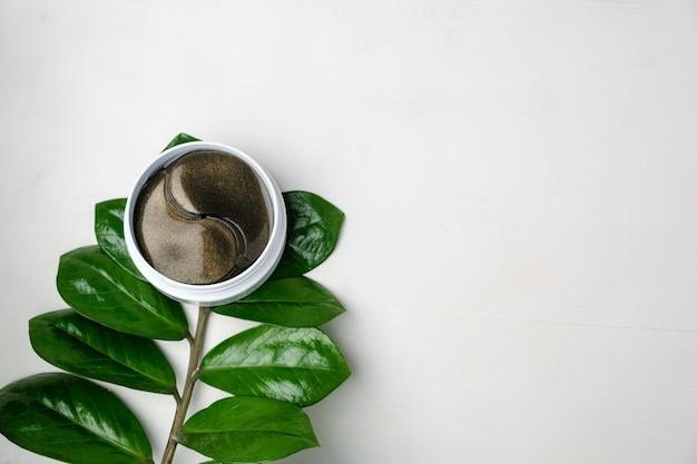 Косметические гидрогелевые патчи для глаз и зеленая ветка с листьями