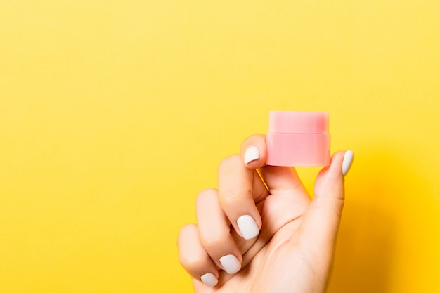 Cosmetics jar in female hand over yellow background