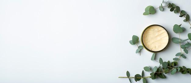 明るい青のバナーの背景にユーカリの葉が付いている化粧品の瓶