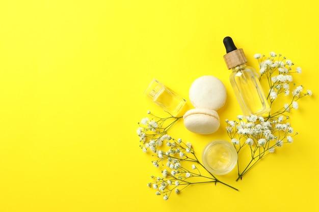Косметика, миндальное печенье и цветы на желтом фоне