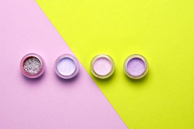 Косметические средства. макияж, мириться. баночки с рассыпчатыми яркими тенями, блестками. розовый, зеленый, сиреневый цвета на сиреневом фоне. крупный план. место для текста или дизайна.