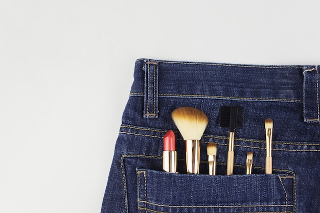 Cosmetics out of the pocket of jeans. makeup objects in jeans pocket