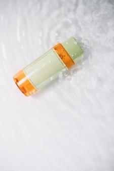 Концепция дизайна упаковки косметики, макет с пустой прозрачной бутылкой на поверхности белой воды