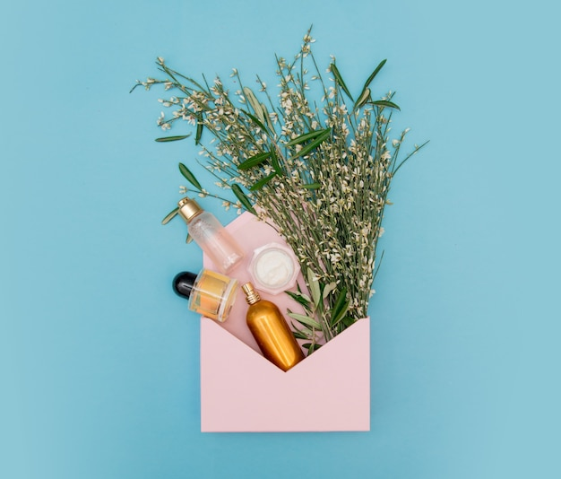 Духи косметики с золотой бутылкой с травами и цветами в розовом конверте на синем фоне. вид сверху