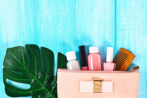 Cosmetics in pink cosmetic bag. lip gloss, cream, nail polish, skin care products on a tro