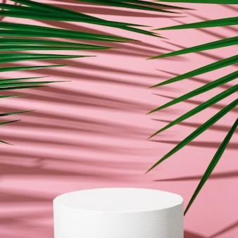 화장품 제품 광고 스탠드. 야자수 잎과 그림자가 있는 분홍색 배경에 기하학적 모양이 있는 흰색 연단을 전시합니다. 제품 포장을 표시하기 위한 빈 받침대. 모형.