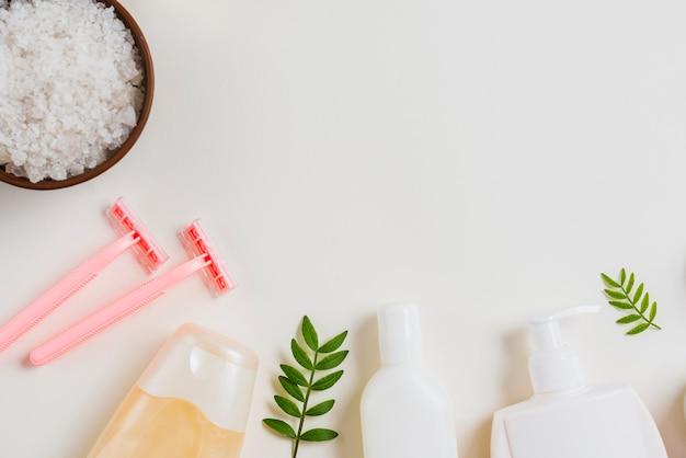 Косметический продукт; бритва; соль на белом фоне