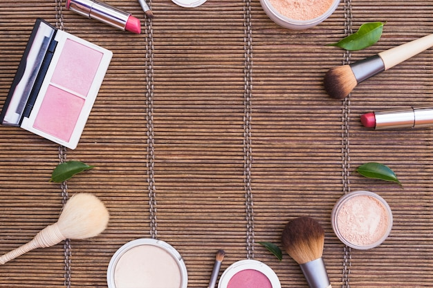 Cosmetics products arranged in circular shape on placemat