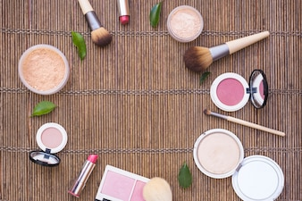 Cosmetics products arranged in circular shape on wooden background