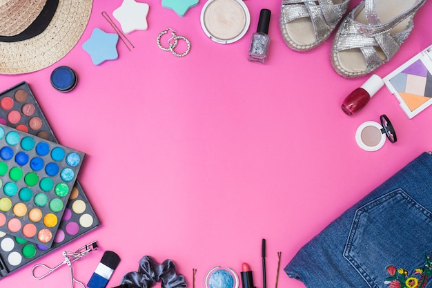 Cosmetics products; pair of footwear; clothes and hat on pink background