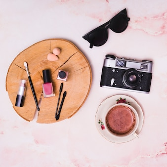 Cosmetics products on tree stump; coffee cup; vintage camera and sunglasses on pink textured background