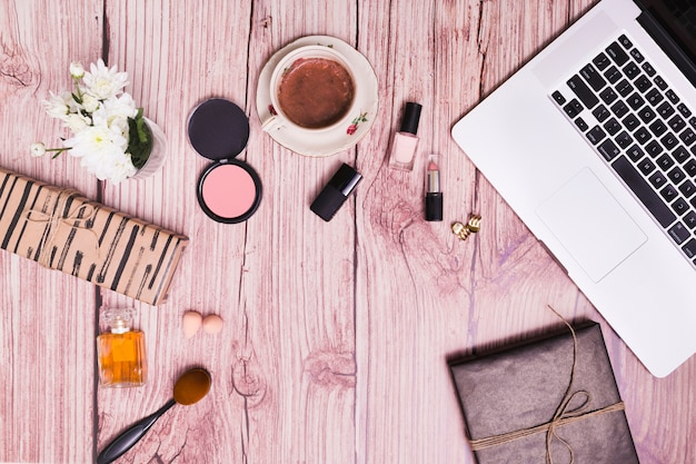 Cosmetics products; vase; diary and laptop on pink wooden textured background