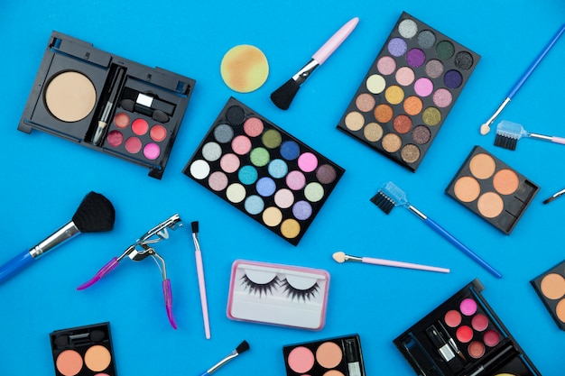 Cosmetics set for women isolated on blue paper background