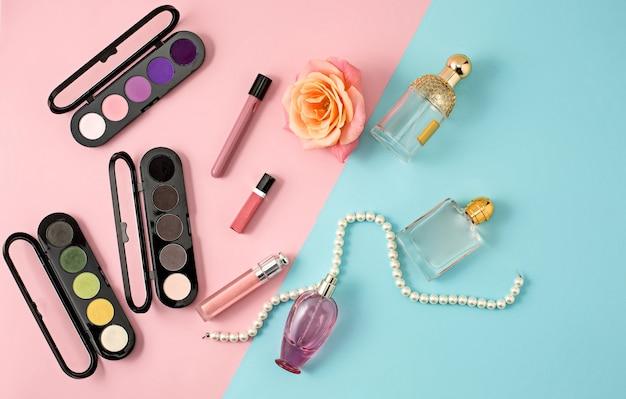 Cosmetics - shadows, lipsticks, perfume on colorful background