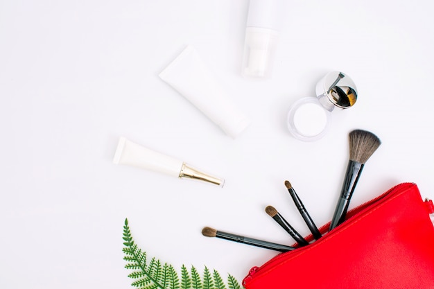 Cosmetics and skin care cream in a red bag with leaves on a white