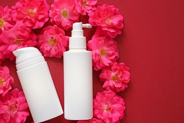 化粧品とスキンケアのモックアップ。ピンクのバラの白い化粧品ボトルにローズエキスとクリームと血清