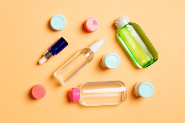 化粧品spaブランドのモックアップ、コピースペース付きの上面図。クリーム色の平らなチューブと瓶のセットは、色付きの背景に横たわっていた。