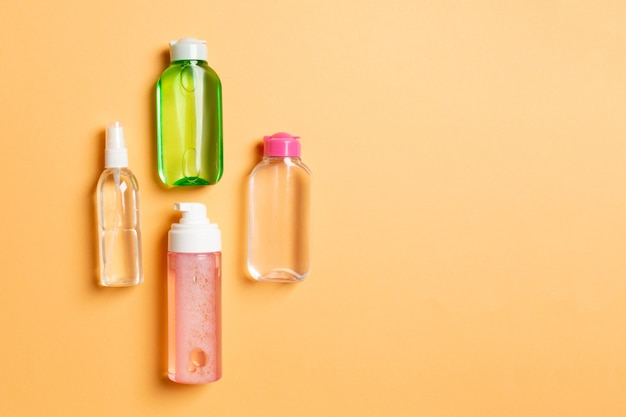 Cosmetics spa branding mock-up, top view with copy space. set of tubes and jars of cream flat lay on colored background.