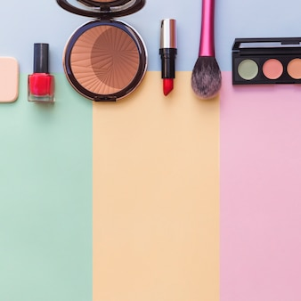 Cosmetics sponge; nail varnish bottle; lipstick; blusher and eye shadow palette on mixed colored background