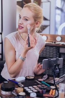 化粧品のトレンド。化粧品のトレンドについて彼女の次のビデオを作るゴージャスな格好良い美容ブロガー