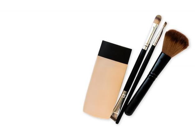 Cosmetics, tube of foundation and brushes