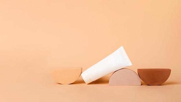 化粧品チューブは幾何学的な表彰台にあります。コピースペース付きの空白のボックス、モックアップ。美しい地球の色。自然な化粧品とヘルスケアの概念。製品を配置するのに適しています。大きなバナー。