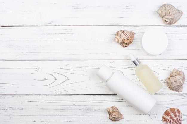 白い木の板に化粧品の白いボトルの日焼け止めと貝殻