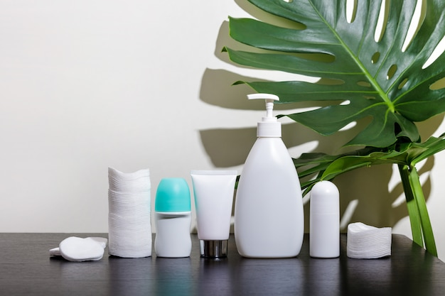 Cosmetics in white tubes and bath products on a black table with tropical leaves.