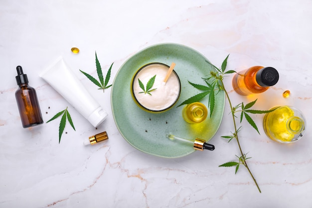 Косметика с маслом каннабиса на бирюзовой тарелке на светлом мраморном фоне копировальный макет