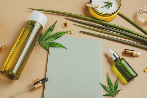 Cosmetics with hemp cbd oil on a beige surface with notebook and marijuana leaves