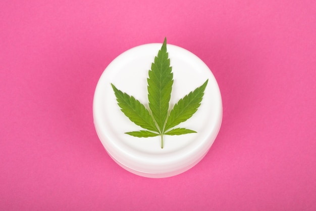 Cosmetics with marijuana extract moisturizer with cannabis leaf on pink background closeup