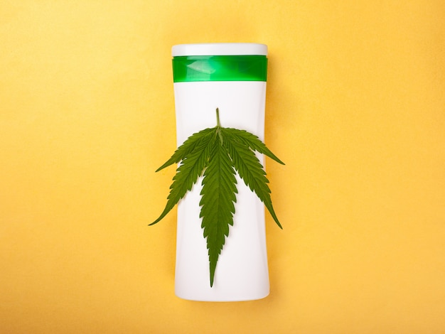 Cosmetics with marijuana extract. skin care, beauty, leaf of cannabis on a white bottle on a yellow background top view.
