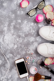 Cosmetics with perfume, phone and sneakers on a gray background with copy space