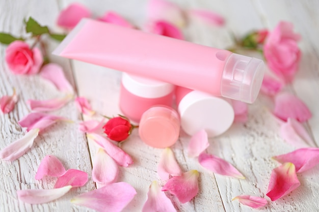 Cosmetics with rose extract. pink face cream, gel for washing with rose extract and rose petals on shabby chic .